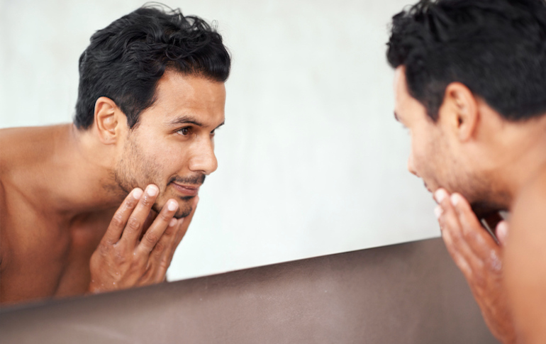 Handsome man looking in mirror admiring his complexion after using brightening, hydrated green tea skincare products