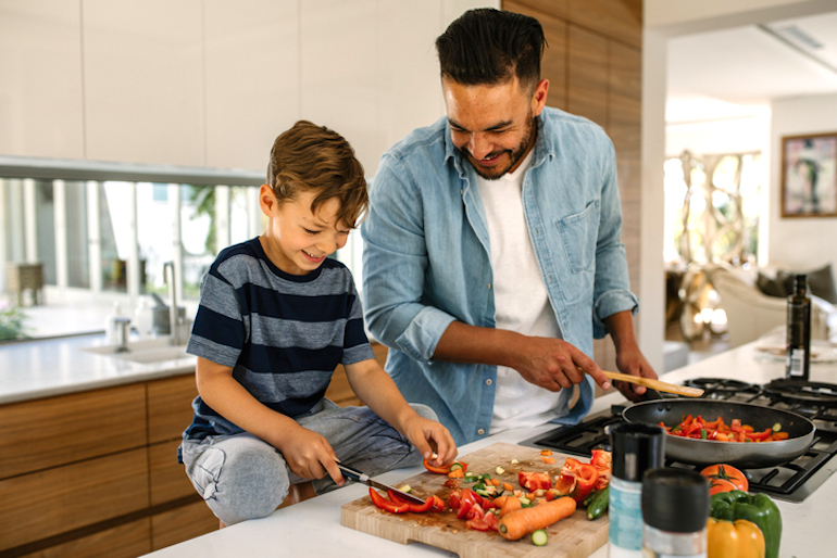 Father and son preparing veggies for a healthy meal