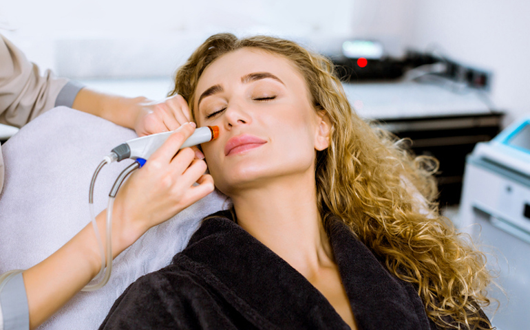 Woman getting HydraFacial at dermatologist's office to treat blind pimples
