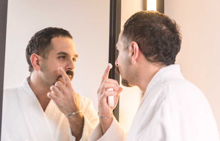 Man applying acne-fighting treatment in the mirror to get rid of blind pimples