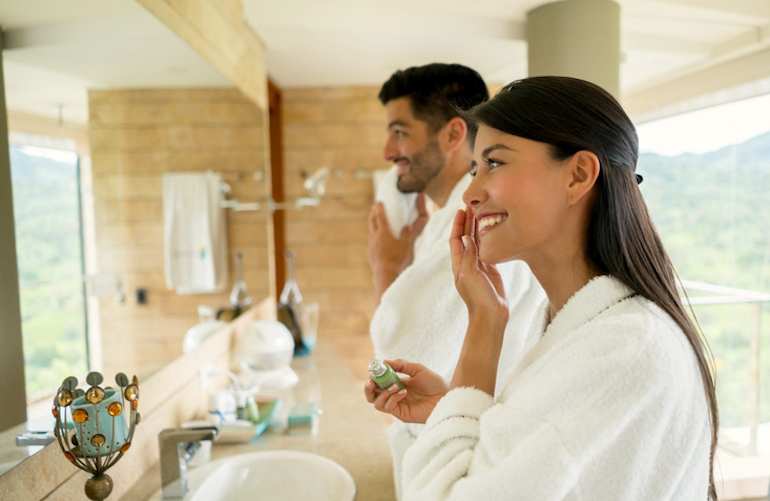 Couple doing their morning skincare routine in the bathroom, which includes the best niacinamide products for skin