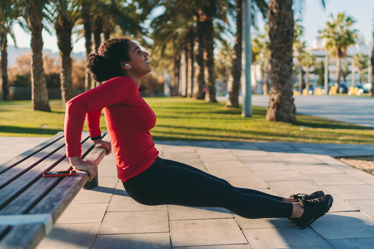 Woman strength training to build muscle in the park