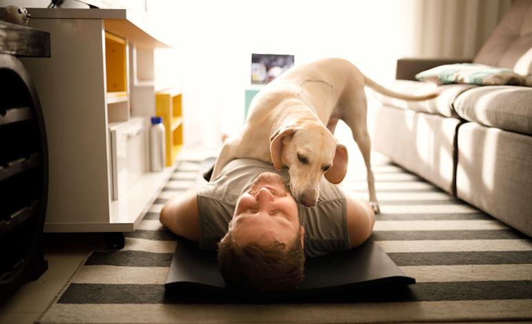 Dog licking its owner while he's on yoga mat, demonstrating the reduced stress health benefit of owning a pet