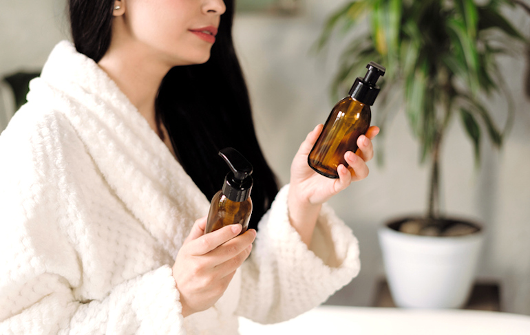 Woman at spa holding two products with Skincare sustainable packaging in glass