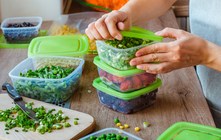 Woman prepping storage containers with produce as an easy sustainable eating tip