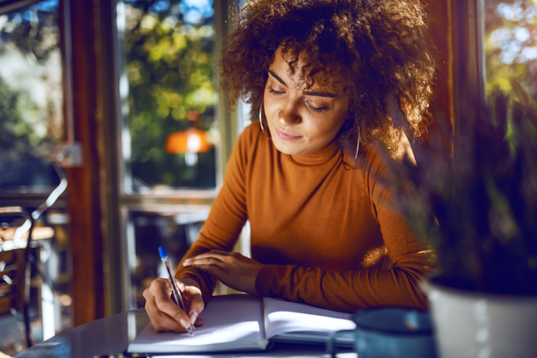 Woman writing at a cafe to illustrate the l-tyrosone benefit of enhanced cognitive performance