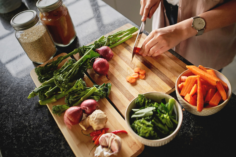 Overhead angled shot on woman chopping vegetables on a cutting board; healthy diet concept