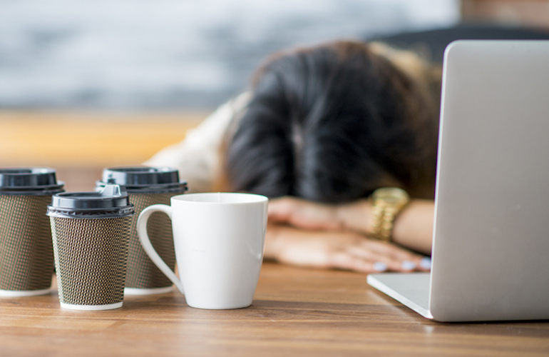 Tired woman crashing at her desk due to coffee slump and poor sleep