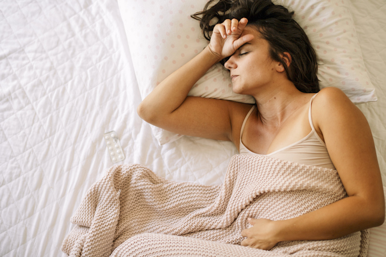 Woman in bed with cramps and throbbing from symptoms of period pain