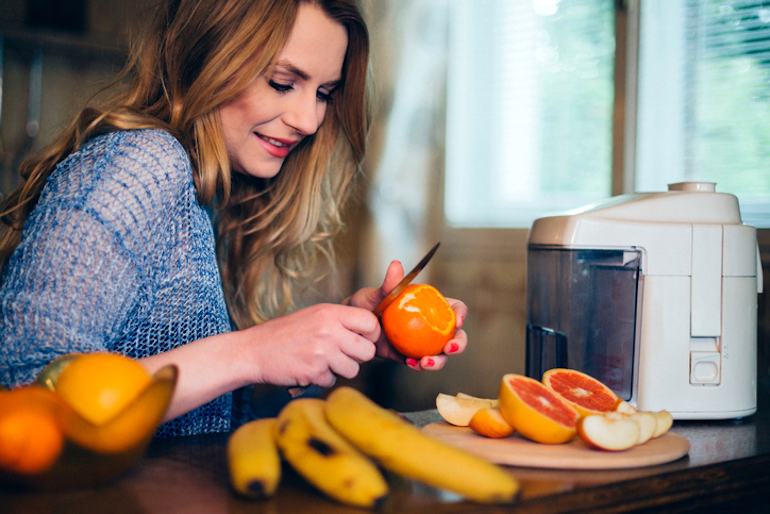 Woman peeling oranges for juicing to experience the benefits of vitamin C for her dull, dry skin