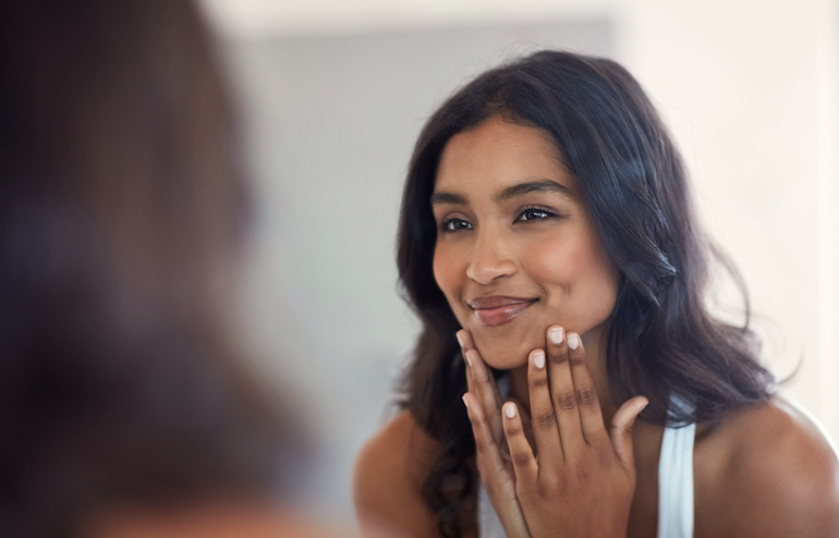 Woman looking at her bright, healthy skin in the mirror thanks to topical vitamin C