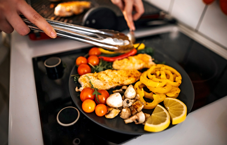 Woman in her 30s preparing a balanced meal with lean chicken and vegetables to maintain muscle mass as she ages