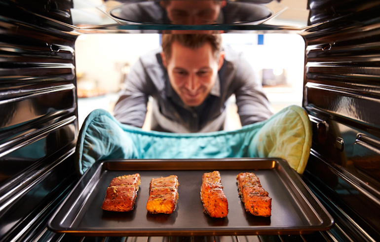Man in his 40s taking salmon out of the oven to benefit from omega-3 intake