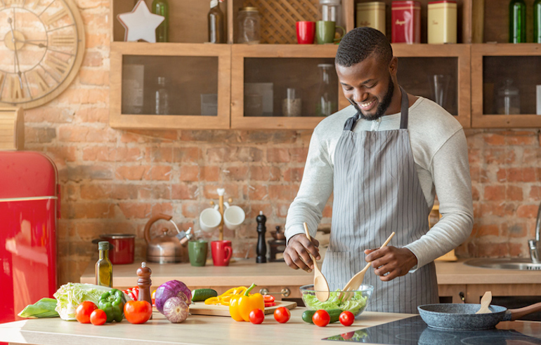 Man in his 20s tossing a colorful salad in the kitchen to get a variety of nutrients; concept of how your nutritional needs change over time