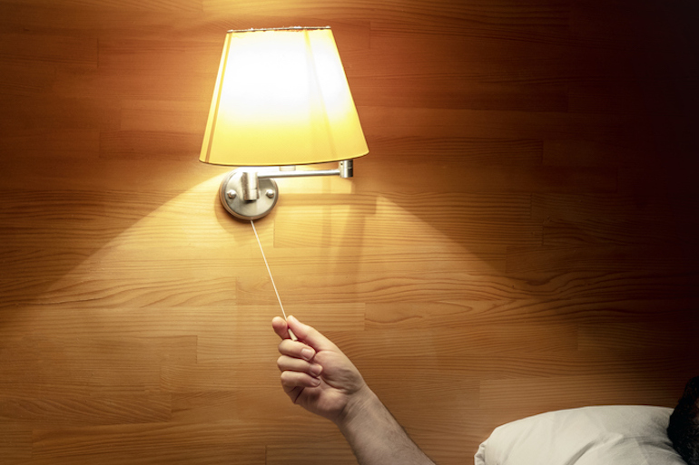 Doctor turning off light in bed to ensure he gets enough sleep to stay healthy and boost immunity