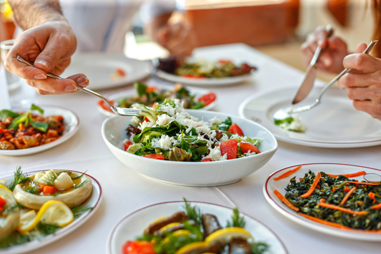 Doctor eating family style, reaching for a salad portion to keep a healthy immune system