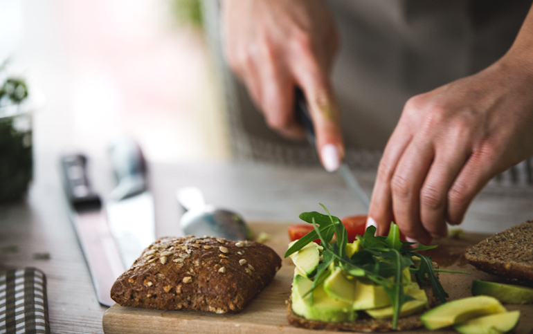 Person making a healthy vegetarian sandwich with avocado, tomato, and arugala to stay healthy via diet