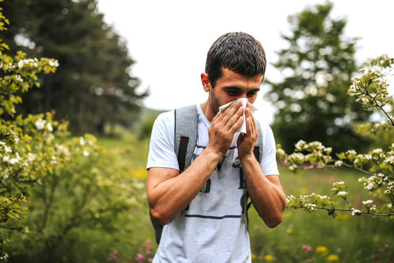 Man blowing his nose outdoors to protect himself from pollen and other antigens, illustrating how the immune system works