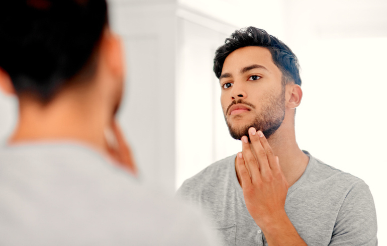 Man looking at his complexion in the bathroom mirror