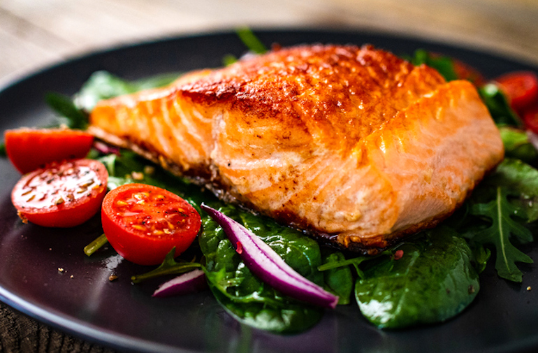 Meal with salmon and spinach, two of the best foods for hair growth and thickness