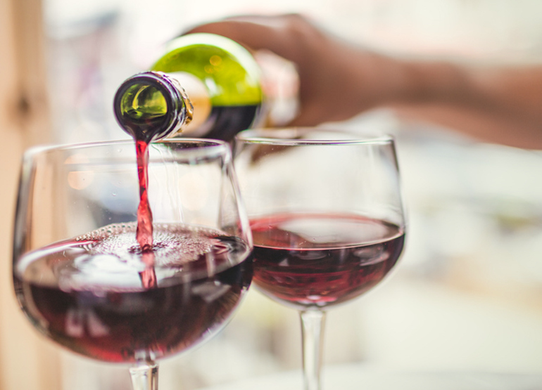 Pouring red wine into two glasses