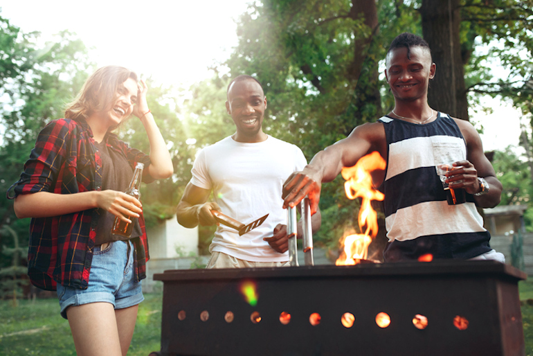 Friends drinking and grilling outdoors, moving food away from the flames