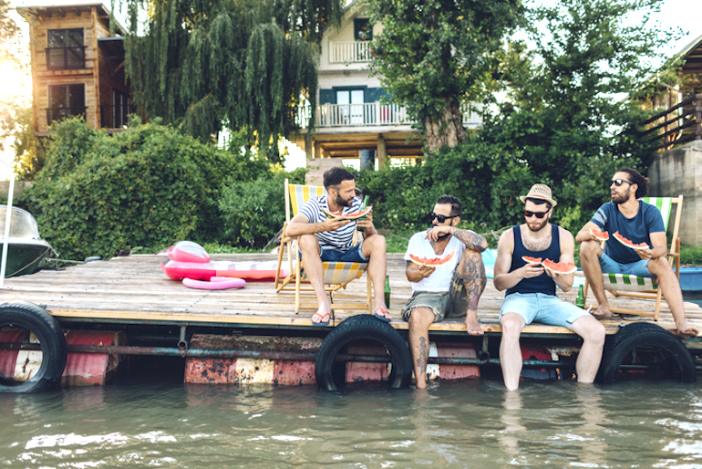Male friends sitting by water eating watermelon for their nutritional benefits