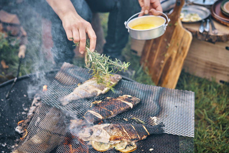 Man grilling fish over a campfire