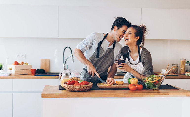 Happy couple cooking together in the kitchen, getting an oxytocin boost from physical intimacy