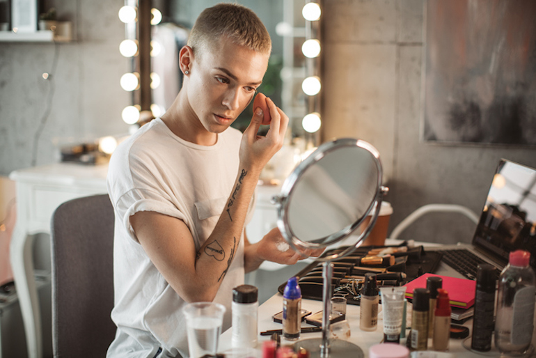 Young man applying foundation at his vanity, wondering what happens if you use expired makeup