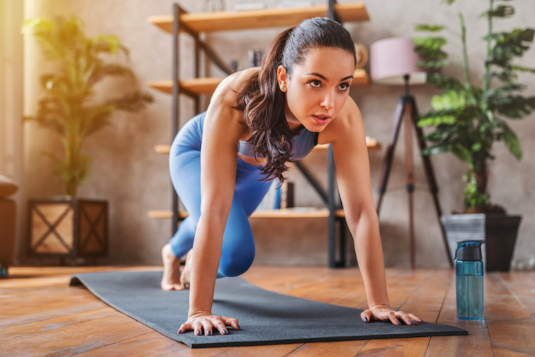 Woman doing yoga at home and staying hydrated with water