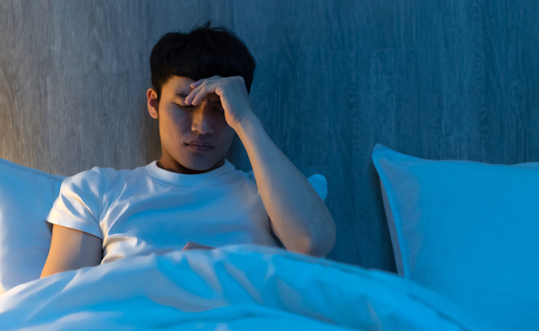 Man suffering from sleep disturbances due to his dependence on energy drinks