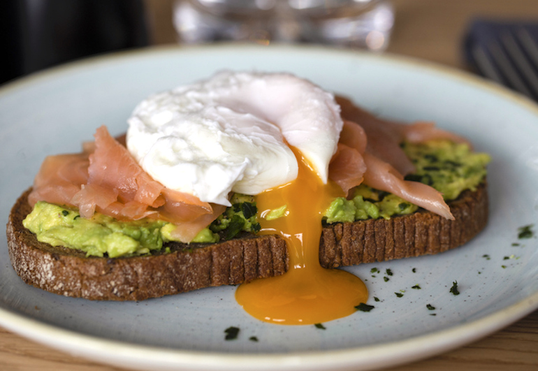 Avocado toast with salmon and poached egg with yolk dripping
