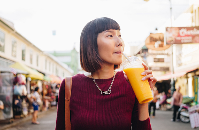 Woman with healthy skin drinking mango juice at outdoor market