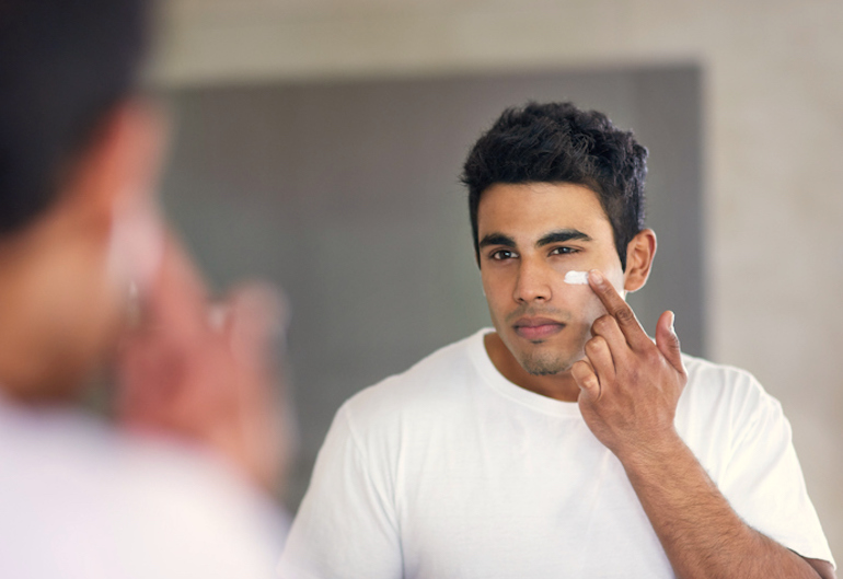Man applying mineral sunscreen to his oily, acne-prone skin