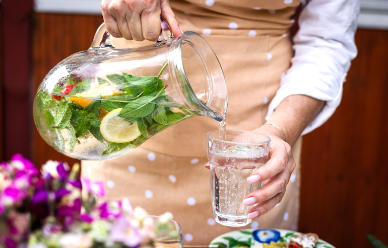 Woman pouring fruit-infused seltzer into glass at garden party
