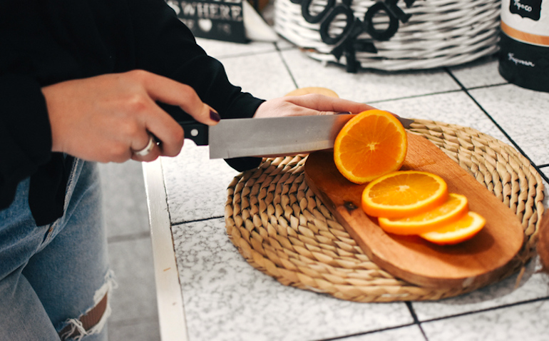 Woman slicing oranges to promote healthy hair growth