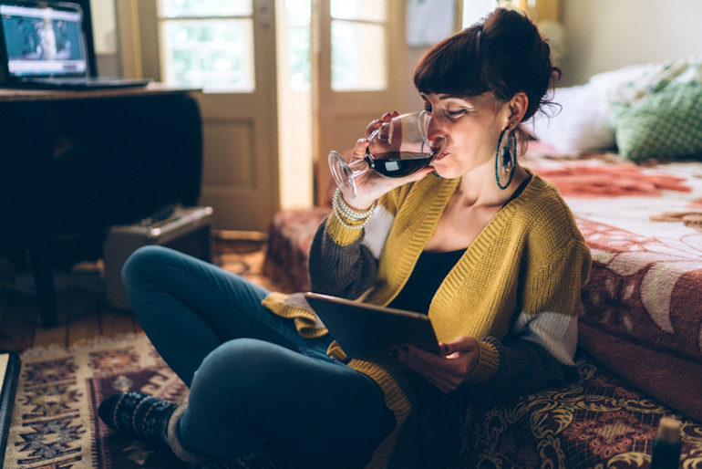 Woman drinking red wine, which can cause teeth to stain and yellow
