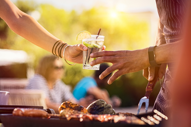 Friends sharing alcoholic spiked seltzer at a barbeque