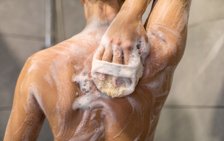 Woman washing her back in the shower with the best body acne treatments