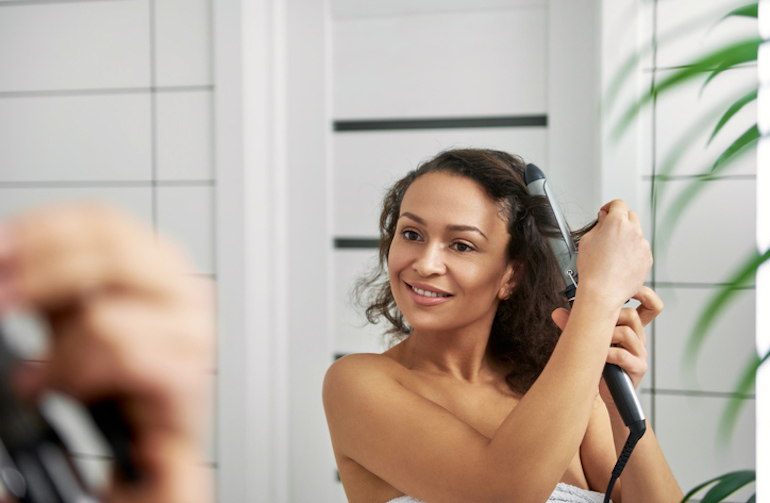 Woman using curling iron to get perfect beach waves