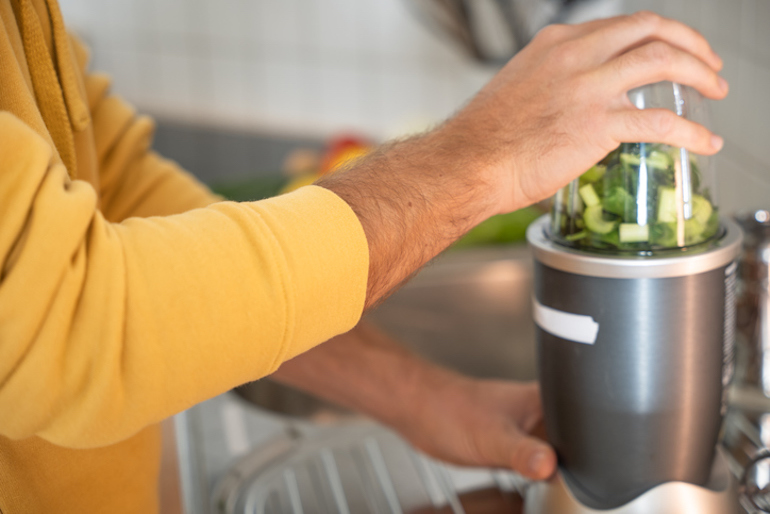 Man making a smoothie with fruits and green vegetables