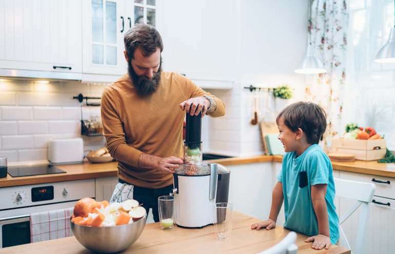 Father and son juicing in the kitchen