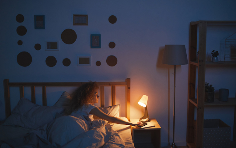 Woman turning off light to improve her sleep and immunity