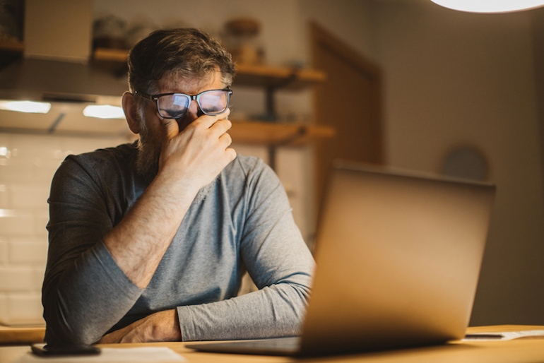 Stressed man working late at night and not getting enough sleep